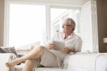 Older man using digital tablet in bedroom — Stock Photo