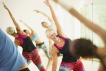 Smiling fitness instructor leading aerobics class stretching arms — Stockfoto
