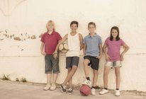 Children with soccer balls leaning against wall — Stock Photo