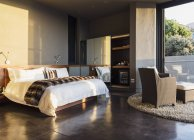 Armchair and bed in modern bedroom — Stockfoto
