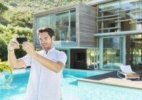 Человек принимает Автопортрет с камеры телефона у бассейна — стоковое фото