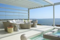Sofa and chairs by swimming pool overlooking ocean — Stock Photo