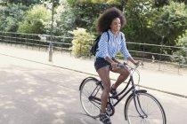 Femme avec afro équitation vélo dans le parc — Photo de stock