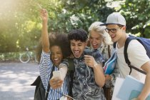 Enthusiastic college students taking selfie in park — Stock Photo