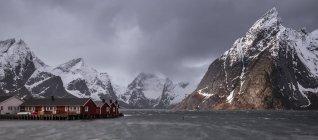 Заснеженный горный хребет выше рыбалка деревня, Hamnoya, Лофотенских островах, Норвегия — стоковое фото