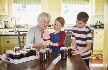 Grandmother canning jam with grandchildren in kitchen — Stock Photo