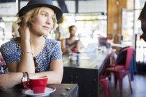 Songeuse femme avec chapeau à café regarder loin dans café — Photo de stock