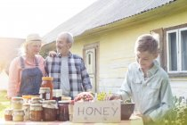 Grandparents and grandson selling honey — Stock Photo