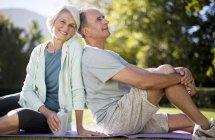 Старший пара, сидячи на килимок йога в парку — стокове фото