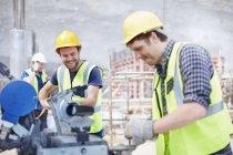 Строители, использующие оборудование на строительной площадке — стоковое фото