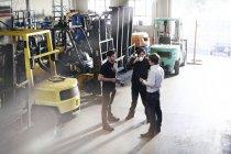 Meccanica ne vicino a carrelli elevatori nel negozio di riparazione auto — Foto stock