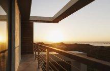 Балкон современного дома с видом на океан на закате — стоковое фото