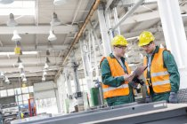 Workers in protective workwear with clipboard in factory — Stock Photo