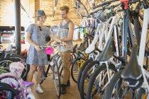 Пара, разглядывая велосипедов в магазине велосипедов — стоковое фото