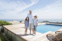 Mayores hombre y nietos sonriendo junto a piscina - foto de stock