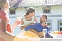 Giovane coppia sorridente che gioca chitarra e bere vino sulla terrazza soleggiata — Foto stock