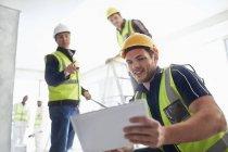 Строители с цифровым планшетом на строительной площадке — стоковое фото