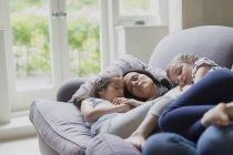 Sereine mère et filles sieste sur le canapé du salon — Photo de stock