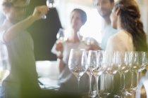 Friends wine tasting in winery tasting room — Stock Photo