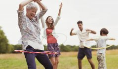 Playful multi-generation family spinning in plastic hoops in field — Stock Photo