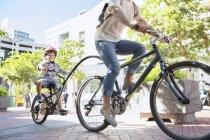 Сын в шлеме катается на тандеме с матерью в городском парке — стоковое фото