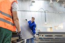 Trabalhadores, carregando o metal de folha em fábrica — Fotografia de Stock