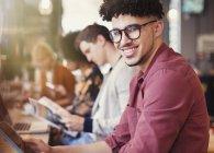 Портрет улыбающийся мужчина с кудрявыми черными волосами с помощью цифровой планшетки в кафе — стоковое фото