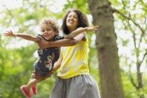 Madre giocosa che vola figlio sotto l'albero — Foto stock