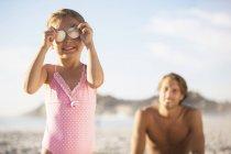 Garota brincando com conchas na praia — Fotografia de Stock