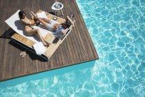 Пара, лежачи на шезлонгу біля басейну, на — стокове фото
