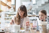 Mother and daughter eating and drinking at cafe table — Stock Photo