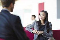 Bem sucedidos empresários adultos conversando no átrio do escritório — Fotografia de Stock