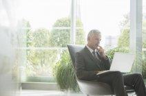 Businessman using laptop in lobby — Stock Photo