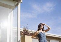 Femme protégeant les yeux à l'extérieur de la maison moderne — Photo de stock