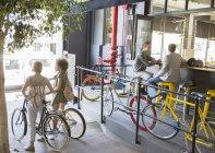 Люди с велосипедами в городских кафе на открытом воздухе — стоковое фото