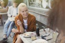 Smiling blonde woman eating dessert at sidewalk cafe — Stock Photo