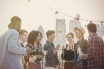 Young adult friends drinking and enjoying rooftop party — Stockfoto