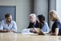 Business people discussing paperwork in conference room — Stock Photo