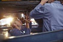 Mechanics working under car in auto repair shop — Stock Photo
