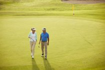 Senior couple walking on golf course — Stock Photo