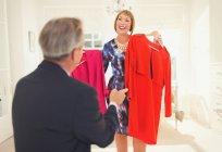 Marido ajudando esposa decidir qual vestido vestir — Fotografia de Stock