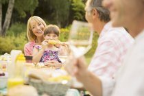 Happy family eating at table in backyard — Stock Photo