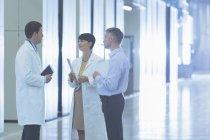 Scientifiques et homme d'affaires, parler dans le couloir de l'usine — Photo de stock