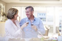 Улыбающаяся пара тостов красные бокалы вина на кухне — стоковое фото