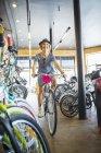 Mulher sorridente andando de bicicleta na loja de bicicletas — Fotografia de Stock