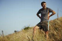 Tired runner taking a break on grassy trail — Stockfoto
