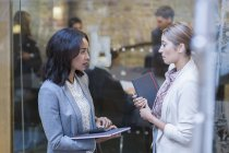 Businesswomen talking outside conference room meeting — Stock Photo