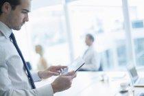 Бизнесмен, использующий цифровой планшет в конференц-зале — стоковое фото