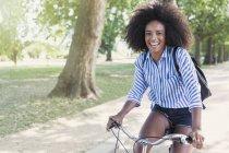 Ritratto donna sorridente con afro in bicicletta nel parco — Foto stock