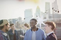 Young men talking at rooftop party — Stock Photo